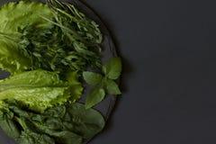 Φρέσκος πράσινος σε ένα πιάτο της πλάκας σε ένα μαύρο υπόβαθρο Στοκ φωτογραφίες με δικαίωμα ελεύθερης χρήσης
