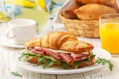 Φρέσκος σάντουιτς-croissant με το ζαμπόν, το arugula, το αγγούρι και το τυρί Στοκ Φωτογραφίες