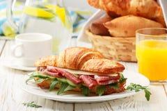 Φρέσκος σάντουιτς-croissant με το ζαμπόν, το arugula, το αγγούρι και το τυρί Στοκ Φωτογραφία