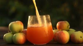 Φρέσκος συμπιεσμένος χυμός μήλων στο διαφανές γυαλί φιλμ μικρού μήκους