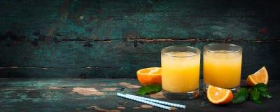 Φρέσκος χυμός από πορτοκάλι με το συντριμμένο πάγο και φρέσκα μπλε άχυρα πορτοκαλιών και σε ένα παλαιό εκλεκτής ποιότητας εξωτικό Στοκ Φωτογραφίες