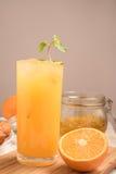 Φρέσκος χυμός από πορτοκάλι σε ένα γυαλί σε μια ξύλινη επιτροπή με τη μαρμελάδα και το μισό πορτοκάλι Στοκ Φωτογραφία