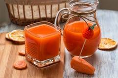 Φρέσκος χυμός καρότων σε ένα γυαλί και μια κανάτα γυαλιού Στοκ Εικόνα