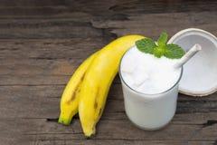 Φρέσκος χυμός καταφερτζήδων βανίλιας κοκτέιλ καρύδων μπανανών και άσπρο ποτό φρούτων μπανανών υγιείς το γούστο yummy στο γυαλί στοκ εικόνα με δικαίωμα ελεύθερης χρήσης