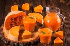 Φρέσκος χυμός κολοκύθας στα όμορφα γυαλιά και κανάτα με τα κομμάτια του ώριμου λαχανικού στο καφετί ξύλινο υπόβαθρο Γλυκός χυμός  Στοκ Εικόνα