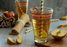 Φρέσκος χυμός μήλων σε ένα γυαλί, άχυρο, κόκκινα μήλα στοκ εικόνες