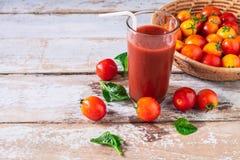 Φρέσκος χυμός ντοματών με τις ντομάτες σε ένα καλάθι στοκ εικόνες