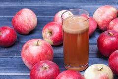 Φρέσκος χυμός της Apple στο γυαλί και μήλα στον ξύλινο πίνακα Στοκ Εικόνες