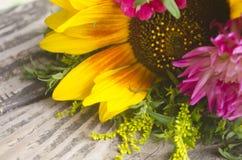 Φρέσκος όμορφος κίτρινος ηλίανθος και ρόδινα wildflowers στο καφετί κατασκευασμένο ξύλινο υπόβαθρο με το διάστημα για το σχέδιό σ Στοκ Εικόνες