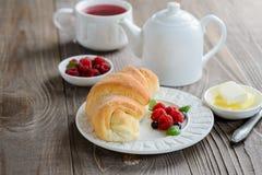 Φρέσκος croissant με το σμέουρο και τσάι για το πρόγευμα στο σκοτεινό ξύλινο πίνακα Στοκ Φωτογραφίες