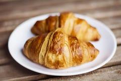 Φρέσκος croissant σε ένα άσπρο πιάτο Στοκ εικόνα με δικαίωμα ελεύθερης χρήσης