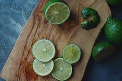 Φρέσκος juicy οργανικός ασβέστης στις φέτες στον ξύλινο πίνακα και το σκοτεινό υπόβαθρο πετρών Ώριμα φρούτα, υγιής τρόπος ζωής, τ στοκ εικόνες