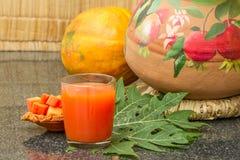 Φρέσκος papaya χυμός στο γυαλί με papaya τα φρούτα, το φύλλο και τις φέτες Στοκ Φωτογραφίες