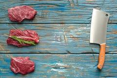 Φρέσκο ακατέργαστο κρέας με το μαχαίρι στο μπλε υπόβαθρο Τοπ-άποψη Στοκ Φωτογραφία