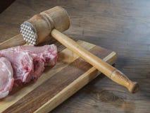 Φρέσκο ακατέργαστο κρέας μπριζολών χοιρινού κρέατος με την παλαιά σφύρα κρέατος στον κάπρο τεμαχισμού στοκ φωτογραφία με δικαίωμα ελεύθερης χρήσης