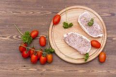 Φρέσκο ακατέργαστο κρέας μπριζόλας με τα διαστήματα, τα χορτάρια και τα λαχανικά στον ξύλινο πίνακα Στοκ Εικόνα
