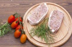 Φρέσκο ακατέργαστο κρέας μπριζόλας με τα διαστήματα, τα χορτάρια και τα λαχανικά στον ξύλινο πίνακα Στοκ Εικόνες