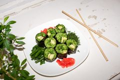 Φρέσκο ακατέργαστο πιάτο τροφίμων Πράσινοι ρόλοι των φύλλων σταφυλιών με τη φυτική πλήρωση στο άσπρο πιάτο στη shabby άσπρη επιφά Στοκ Εικόνα