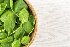 Φρέσκο ακατέργαστο πράσινο σπανάκι μωρών στο γκρίζο ξύλο Στοκ Φωτογραφίες