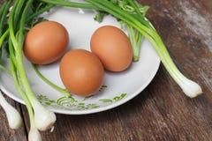 Φρέσκο αυγό κοτόπουλου στενό σε έναν επάνω πιάτων και κρεμμύδι στον ξύλινο πίνακα Στοκ Εικόνες