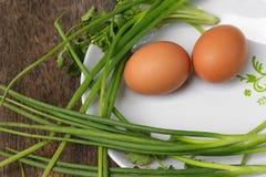 Φρέσκο αυγό κοτόπουλου στενό σε έναν επάνω πιάτων και κρεμμύδι στον ξύλινο πίνακα Στοκ εικόνα με δικαίωμα ελεύθερης χρήσης
