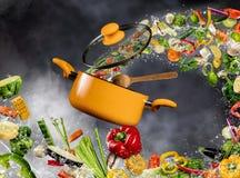 Φρέσκο λαχανικό που πετά σε ένα δοχείο στο σκοτεινό υπόβαθρο Στοκ Φωτογραφία