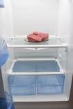 Φρέσκο βόειο κρέας σε ένα πιάτο, σε ένα κενό ψυγείο Στοκ Εικόνες