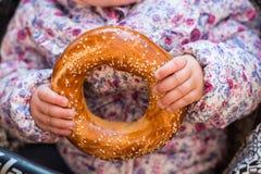 Φρέσκο, γλυκό bagel στα χέρια των μικρών παιδιών Στοκ φωτογραφία με δικαίωμα ελεύθερης χρήσης