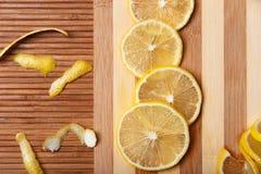 Φρέσκο κίτρινο λεμόνι με τις φέτες στον ξύλινο πίνακα κουζινών μπαμπού Στοκ Εικόνες