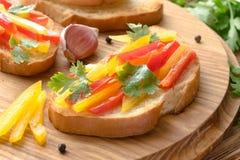 Φρέσκο και νόστιμο bruschetta με το πιπέρι χρώματος, κορίανδρο στοκ εικόνες