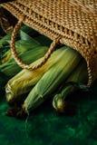 Φρέσκο καλαμπόκι στους σπάδικες στον πράσινο ξύλινο πίνακα Στοκ Εικόνα
