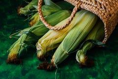 Φρέσκο καλαμπόκι στους σπάδικες στον πράσινο ξύλινο πίνακα Στοκ Φωτογραφίες