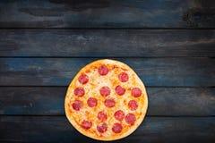 Φρέσκο κλασικό pepperoni pizzai σε ένα σκοτεινό ξύλινο υπόβαθρο Τοπ κατώτατος προσανατολισμός άποψης Στοκ φωτογραφίες με δικαίωμα ελεύθερης χρήσης