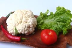 Φρέσκο κουνουπίδι, ντομάτα, φύλλα σαλάτας και άλλα λαχανικά στον ξύλινο πίνακα Έτοιμος για το μαγείρεμα Χορτοφάγα τρόφιμα Στοκ Φωτογραφίες