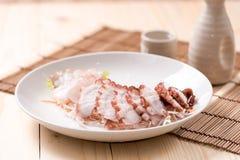 Φρέσκο κρύο sashimi χταποδιών στο πιάτο στον ξύλινο πίνακα στοκ εικόνα
