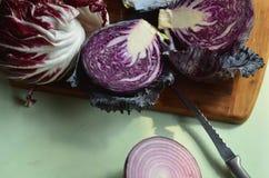Φρέσκο κόκκινο λάχανο περικοπών στον τέμνοντα πίνακα, κόκκινο κρεμμύδι, κόκκινο radicchio Στοκ Εικόνα