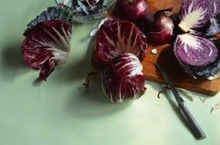 Φρέσκο κόκκινο λάχανο περικοπών στον τέμνοντα πίνακα, κόκκινο κρεμμύδι, κόκκινο radicchio Στοκ Φωτογραφία