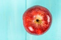 Φρέσκο κόκκινο - η εύγευστη Apple στον τυρκουάζ πίνακα Στοκ Εικόνες