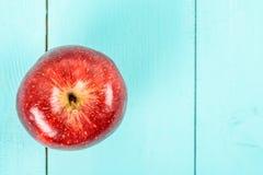Φρέσκο κόκκινο - η εύγευστη Apple στον τυρκουάζ πίνακα Στοκ Φωτογραφία