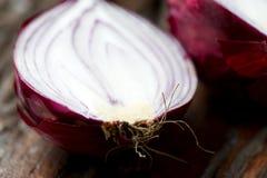 Φρέσκο κόκκινο κρεμμύδι που κόβεται παλαιό ξύλινο επιτραπέζιο στενό σε έναν επάνω Στοκ εικόνες με δικαίωμα ελεύθερης χρήσης