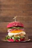 Φρέσκο κόκκινο burger κοτόπουλου με τη μοτσαρέλα και arugula στο ξύλινο υπόβαθρο Στοκ φωτογραφία με δικαίωμα ελεύθερης χρήσης