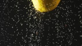 Φρέσκο λεμόνι που περιέρχεται στο νερό στο μαύρο υπόβαθρο Εσπεριδοειδή στο νερό με τις φυσαλίδες Οργανική τροφή, υγιής τρόπος ζωή απόθεμα βίντεο