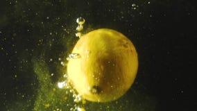 Φρέσκο λεμόνι που περιέρχεται στο νερό με τη γύρη στο μαύρο υπόβαθρο Εσπεριδοειδή φρέσκα στο νερό με τις φυσαλίδες E απόθεμα βίντεο