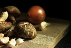 Φρέσκο μανιτάρι με το σκόρδο και κρεμμύδι στον τεμαχίζοντας πίνακα Στοκ Φωτογραφία