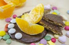 Φρέσκο πορτοκάλι, μπισκότα και ζωηρόχρωμα bonbons Στοκ φωτογραφίες με δικαίωμα ελεύθερης χρήσης