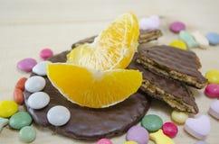Φρέσκο πορτοκάλι, μπισκότα και ζωηρόχρωμα bonbons Στοκ Εικόνες