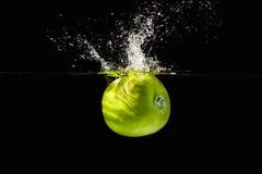 Φρέσκο πράσινο μήλο που εμπίπτει στο ύδωρ με τον παφλασμό Στοκ φωτογραφία με δικαίωμα ελεύθερης χρήσης