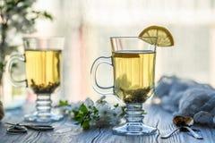 φρέσκο πράσινο τσάι Φλυτζάνι τσαγιού με το πράσινο φύλλο τσαγιού στον ξύλινο πίνακα Τσάι με το λεμόνι Στοκ Εικόνες