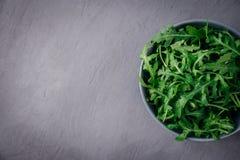 Φρέσκο πράσινο arugula στο κύπελλο στο γκρίζο υπόβαθρο πετρών Το Arugula είναι πλούσιο στις βιταμίνες και ιχνοστοιχεία Εκλεκτική  Στοκ φωτογραφία με δικαίωμα ελεύθερης χρήσης