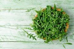 Φρέσκο πράσινο arugula στο κύπελλο στον ξύλινο πίνακα Στοκ φωτογραφία με δικαίωμα ελεύθερης χρήσης